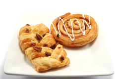 Danish Pastries. Cinnamon Swirl and Maple/Pecan danish pastries on a square plate royalty free stock images