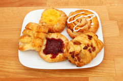 Danish pastries on a plate. Selection of Danish pastries on a plate on a wooden tabletop Royalty Free Stock Photos