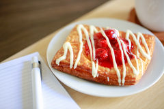 Danish pastry with a cup of hot tea and a pen and small notebook on wood table in morning time. Cherry danish pastry with a cup of hot tea and a pen and small Stock Photography