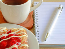 Danish pastry with a cup of hot tea and a pen and small notebook on wood table in morning time and red heart for valentine Stock Photos