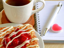 Danish pastry with a cup of hot tea and a pen and small notebook on wood table in morning time and red heart for valentine Royalty Free Stock Images