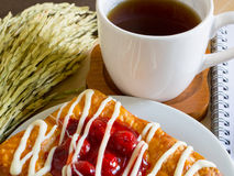 Danish pastry with a cup of tea and ear of rice decoration Stock Photo