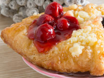 Danish pastry on wooden table. Fruit, cherry danish on wooden table Royalty Free Stock Image