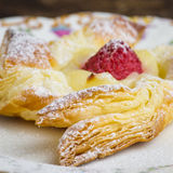 Danish puff pastry pinwheels with vanilla pastry cream and raspb. Homemade danish puff pastry pinwheels with vanilla pastry cream and raspberries and icing sugar Stock Photo