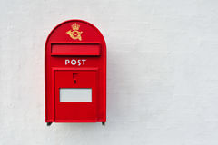 Danish red post box. Danish red mailbox on white wall background royalty free stock photography