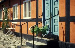 Danish red timbered house, Bornholm in Denmark. Red timbered wall, blue doors and a dog sleeping on stone stairs on small classic Danish living house in Svaneke stock photos