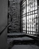 Light shines through cast iron barred door in stone passage. Dank passage ends with filligreed iron gated door. Shadows fall from stone steps in the black and stock image