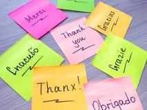 Dank u bericht op verschillende talen op kleverige nota over houten achtergrond stock afbeeldingen