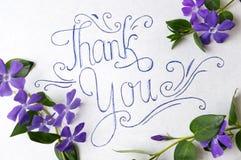 Dank u nota nemen van omringd door purpere bloemen royalty-vrije stock afbeeldingen