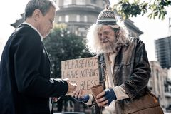 Dankbare langharige oude mens die lege koffiekop voorstellen stock fotografie