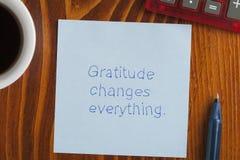 Dankbarkeit ändert alles, das auf eine Anmerkung geschrieben wird stockfotos