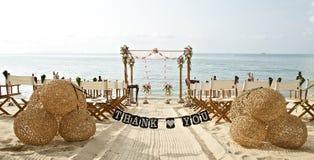 Danke abfaßt Fahne an den schönen Strandhochzeits-Einrichtungsstühlen Stockbild