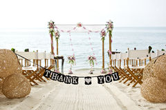 Danke abfaßt Fahne an den schönen Strandhochzeits-Einrichtungsstühlen Stockfotografie