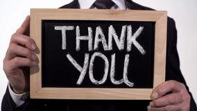 Danke geschrieben auf Tafel in Geschäftsmannhände, Spendenanerkennung stockfotos