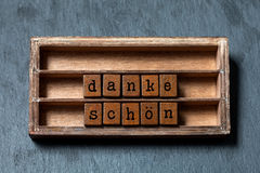 Danke schon Thank you in German translation. Vintage box, wooden cubes thankful phrase message written with old style. Letters. Gray stone textured background Royalty Free Stock Images