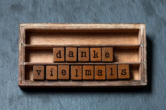 Danke vielmals. Thank you very much or great thanks in German translation. Vintage box, wooden cubes phrase written with. Old style letters. Gray stone textured Stock Photo