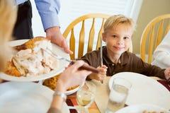Danksagung: Hungriger Junge hält Tafelsilber beim Warten auf Dinn stockbild