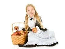 Danksagung: Lächelndes Pilger-Mädchen, das Korb von Äpfeln hält Lizenzfreie Stockfotografie