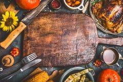 Danksagungsabendessenhintergrund mit Truthahn, Soße, grillte Gemüse, Mais, Tischbesteck, Kürbis, Fallblätter und blüht arrangemen Stockfotografie