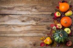 Danksagungsdekor mit grünem Kürbis, orange Zwiebelkürbis, Fallblättern, Äpfeln und Birnen auf dem rustikalen hölzernen Hintergrun stockfotografie