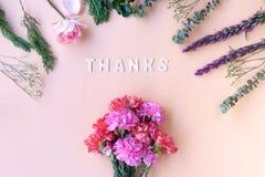 Dankt hölzernem Wort mit Gartennelken der frischen Blumen auf weicher Creme Stockbilder