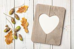 Dankzeggingskaart met eiken bladeren, eikels en hart gestalte gegeven kader stock foto