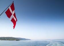 Danmark flagga från baksidan av ett fartyg som lämnar copenhagen Arkivbild