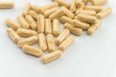 Danno medicinale in capsule su fondo bianco, fuoco selettivo immagini stock