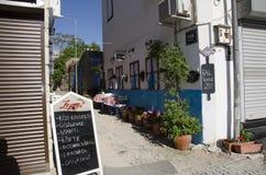 Dans Alacati il y a des cafés, couverts et des menues de nourriture devant les hôtels Images libres de droits