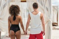 Dans-amour jeune de couples détendant sur la plage confortable Photos stock