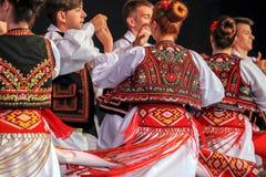 Dans av unga rumänska dansare i traditionell dräkt arkivbild