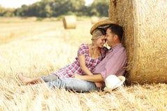 Dans de jeunes couples d'amour sur des meules de foin dans des chapeaux de cowboy Image libre de droits