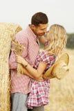 Dans de jeunes couples d'amour sur des meules de foin dans des chapeaux de cowboy Image stock