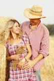 Dans de jeunes couples d'amour sur des meules de foin dans des chapeaux de cowboy Photographie stock libre de droits