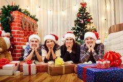 Dans des amis de Noël se trouvant sur le plancher, souriant dans les chapeaux o Images stock