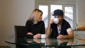 Dans des couples d'amour ayant le café et l'embrassant à la maison pendant le matin banque de vidéos