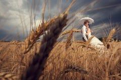 Dans des couples d'amour dans le beau domaine de blé avec le ciel dramatique Photos libres de droits