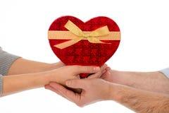 Dans des couples d'amour tenant un coeur d'amour sur le fond blanc Image stock