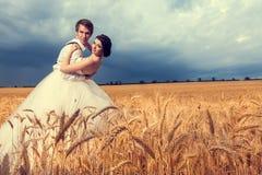 Dans des jeunes mariés d'amour dans le domaine de blé avec le ciel bleu dans le dos Photo stock