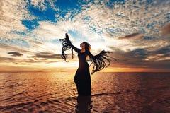 Dans för elegant kvinna på vatten Solnedgång och silhouette arkivfoton