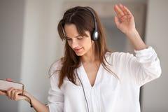 Dans för kvinnainnehavtelefon som lyssnar till musik som spelar i headph royaltyfri bild