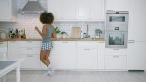 Dans för ung kvinna i kök med smartphonen stock video