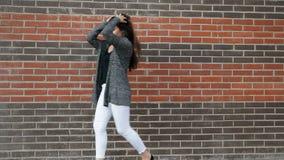Dans för ung kvinna mot en tegelstenvägg som går runt om staden arkivfilmer