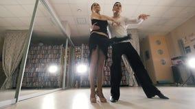 Dans för ung man och kvinnaoch praktiserande latin - amerikansk dans i dräkter i studion, ultrarapid, i handling lager videofilmer