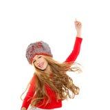 Dans för ungeflickavinter med den röda skjorta- och pälshatten Royaltyfri Foto