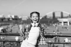 Dans f?r din lycka Little musikventilator Lilla flickan lyssnar till utomhus- musik lycklig flicka little Lyckliga barnkl?der fotografering för bildbyråer