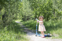 Dans fille bouclée de forêt de bouleau d'été la petite montant un scooter Photo libre de droits