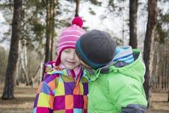 Dans garçon de forêt d'automne le petit embrassant sa fille d'amie Image libre de droits