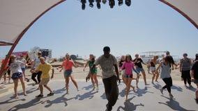 Dans hoofdklasse op hiphop voor een groep mensen van een professionele danser op de kust stock video
