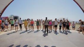 Dans hoofdklasse op hiphop voor een groep mensen van een professionele danser op de kust stock footage